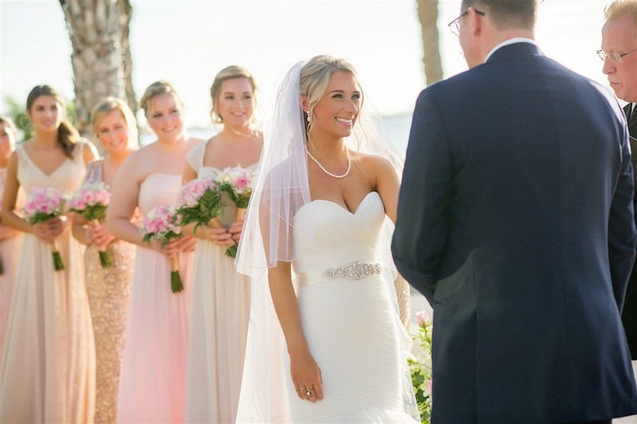Outdoor Waterfront Wedding Ceremony Portrait with Sweetheart Dress with Silver Jeweled Belt, Long-stemmed White and Pink Bouquets with Fern Greenery and Mismatched Pink, Cream, Gold, and Sequined Bridesmaids Dresses