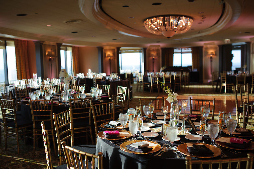 Elegant Wedding Reception with Black Linens, Simple White and Purple Orchid Centerpieces in Tall Glass Vases with Tall Glass Candleholders, and Gold Chiavari Chairs | Downtown Tampa Wedding Reception Venue The Tampa Club