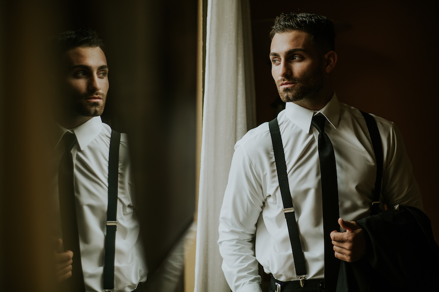 Groom Getting Ready Dramatic Portrait with Suspenders Suit and Skinny Black Tie Tampa Bay Wedding Photographer Brandi Image Photography