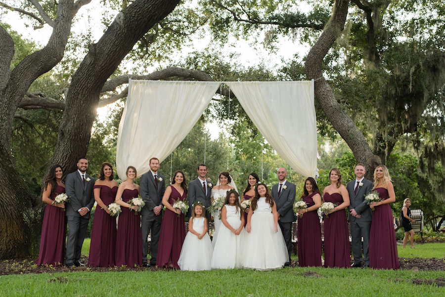 Grey White and Bordeaux Outdoor Wedding Party Portrait with Mismatched Dessy Bridesmaids Dresses and White Drapery Ceremony Arch and Flower Girls   Tampa Bay Wedding Venue Tampa Garden Club   Photographer Caroline & Evan Photography
