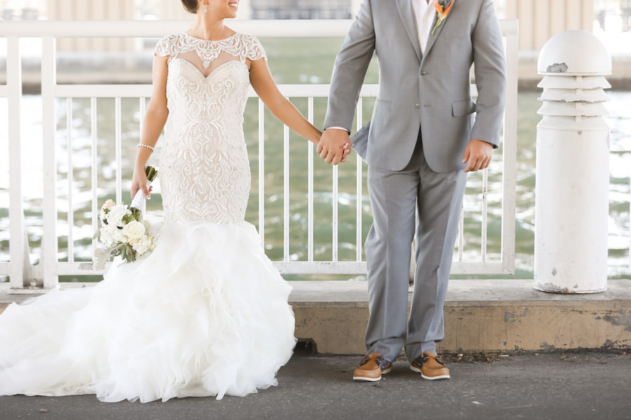 Outdoor Waterside Wedding Portrait with Beaded Mermaid Adrianna Papell Wedding Dress with Ivory Rose Bouquet with Succulents, Groom in Gray Suit with Brown Boat Shoes and Bird of Paradise Boutonnière