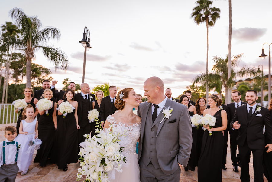 Outdoor Wedding Party Portrait with Black Mismatched Bridesmaids Dresses and White Bouquets and Gray Groomsmen Suit with White Rose and Feather Boutonniere   Tampa Bay Wedding