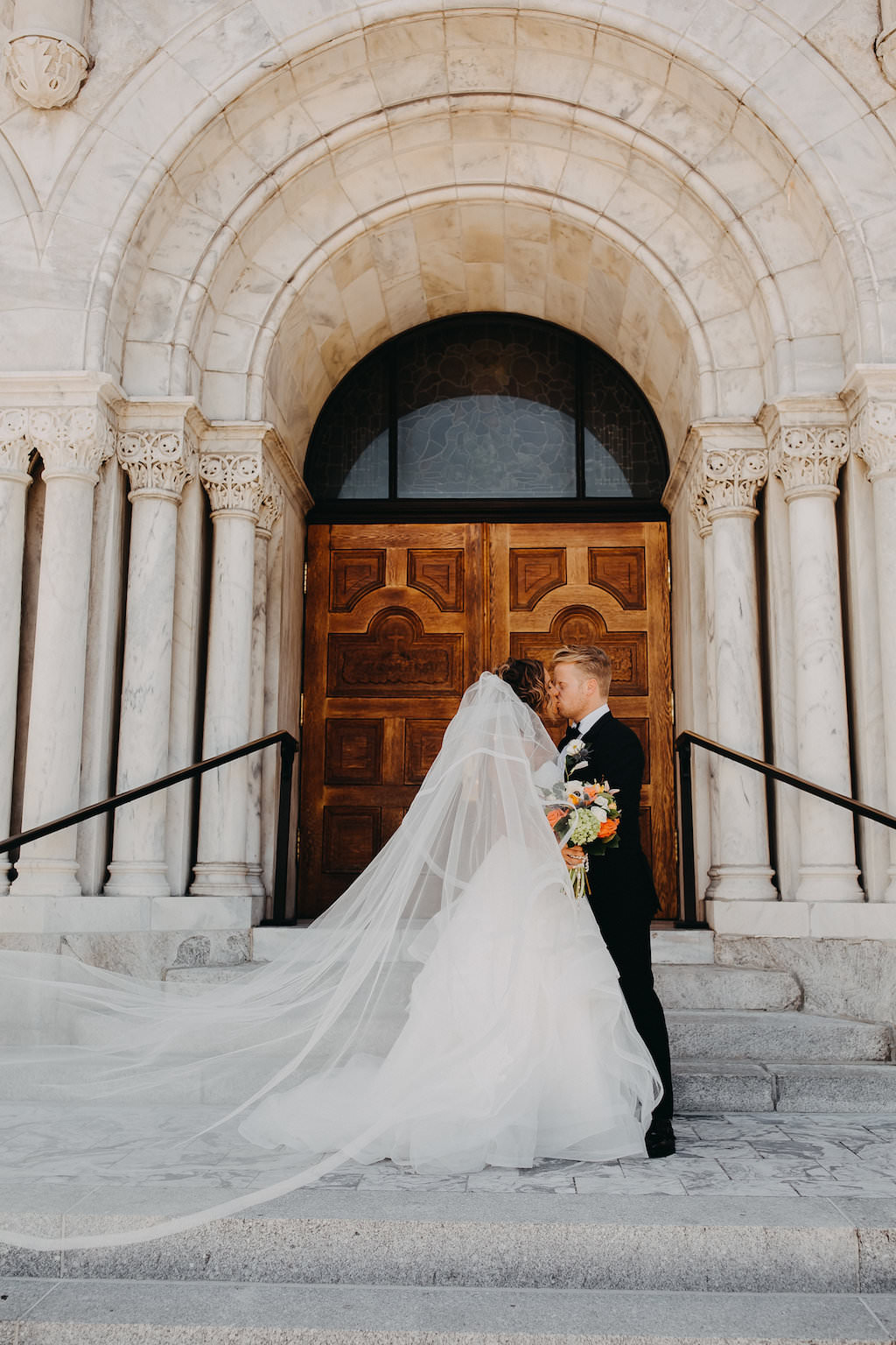 Outdoor Church Steps Wedding Ceremony Exit Portrait with Tropical Bouquet   Downtown Tampa Wedding Photographer Rad Red Creative   Traditional Church Wedding Ceremony Portrait with Orange and Greenery Tropical Bouquet, Stella York Wedding Dress with Layered Skirt   Downtown Tampa Wedding Photographer Rad Red Creative   Sacred Heart Catholic Church