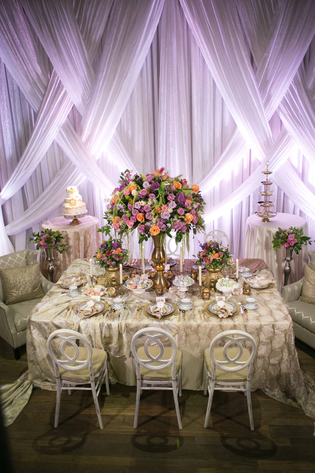 Modern Wedding Reception with Unique Vintage Inspired Furniture and Linens, Tropical Orange, Pink, and Purple Rose with Greenery Centerpieces in Tall Gold Vases, and Drapery with Purple Uplighting | St. Petersburg Wedding Venue NOVA 535 | Planner UNIQUE Weddings and Events | Photographer Carrie Wildes Photography
