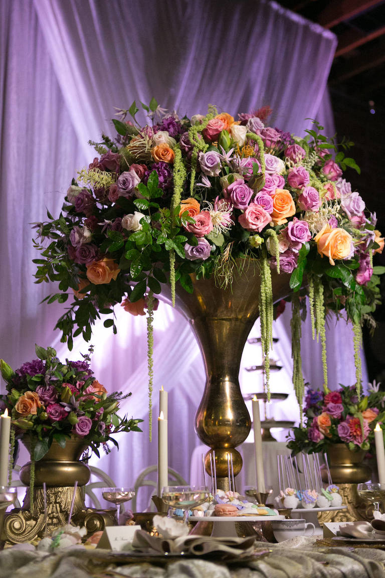Tall Wedding Reception Centerpiece with Pink, Orange, and Purple Roses with Tropical Greenery