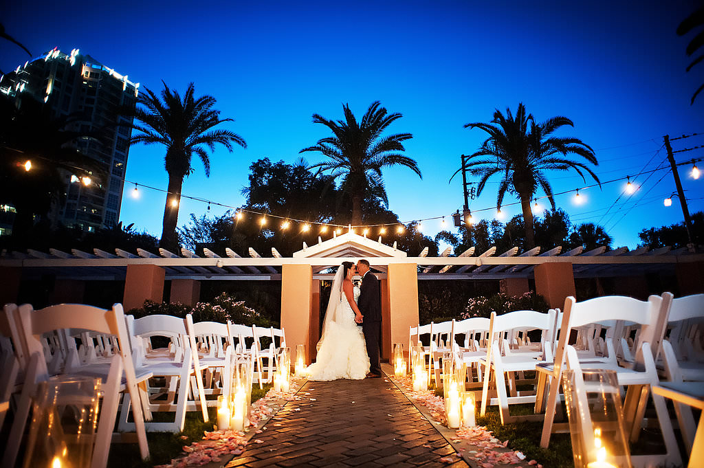 Outdoor Nighttime Courtyard Wedding Ceremony Portrait with Pink Rose Petal Aisle, String LIghts, White Folding Chairs, and Tall Hurricane Candle Holders | St Pete Wedding Photographer Limelight Photography | Tampa Bay Hotel Wedding Venue Vinoy Renaissance