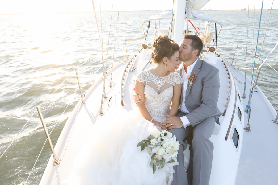 Outdoor Wedding Portrait on Yacht with Beaded Lace Adrianna Papell Wedding Dress and Ivory and Anemone Bouquet, Groom in Grey Suit with Bird of Paradise Boutonnière | St Pete Wedding Venue Isla del Sol Yacht & Country Club