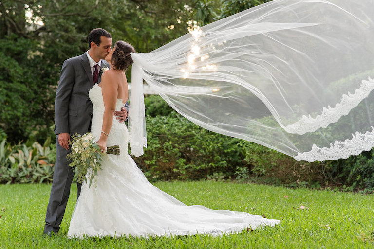 Outdoor Garden Ceremony Portrait with Strapless Mermaid Allure Wedding Dress with Long Lace Veil, Grey Grooms Suit with Bordeaux Tie   Tampa Bay Wedding Photographer Caroline & Evan Photography   Ceremony Venue Tampa Garden Club