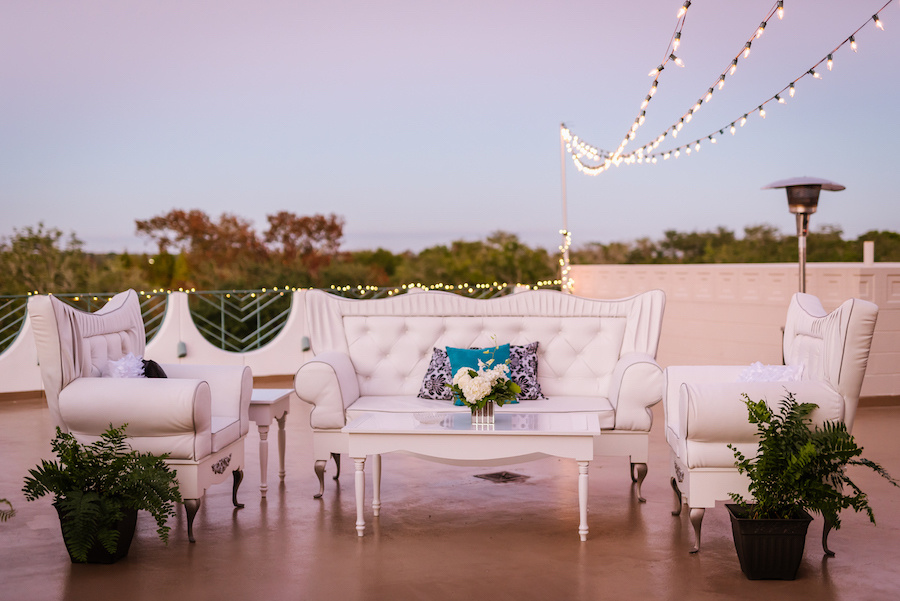 1920s Vintage Inspired Wedding Decor White Lounge Furniture with Ferns and String Lights and Small White Floral Centerpiece   Clearwater Wedding Venue Ruth Eckerd Hall