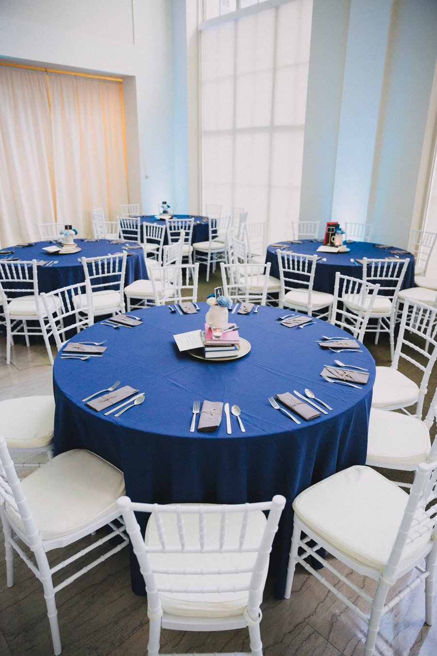Modern Wedding Reception Round Table Decor with White Chiavari Chairs, Gray Napkins, Blue Linen, and Creative Books and Guestbook with Pens Centerpiece