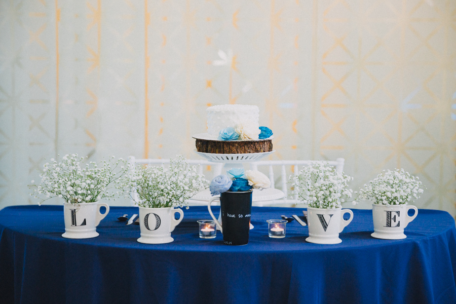 Bride and Groom Wedding Reception Blue and White Table Decor with LOVE Ceramic Letter Coffee Mugs with Babys Breath, Small Blue and White Flowers, and Small Round White Wedding Cake on White Cake Stand