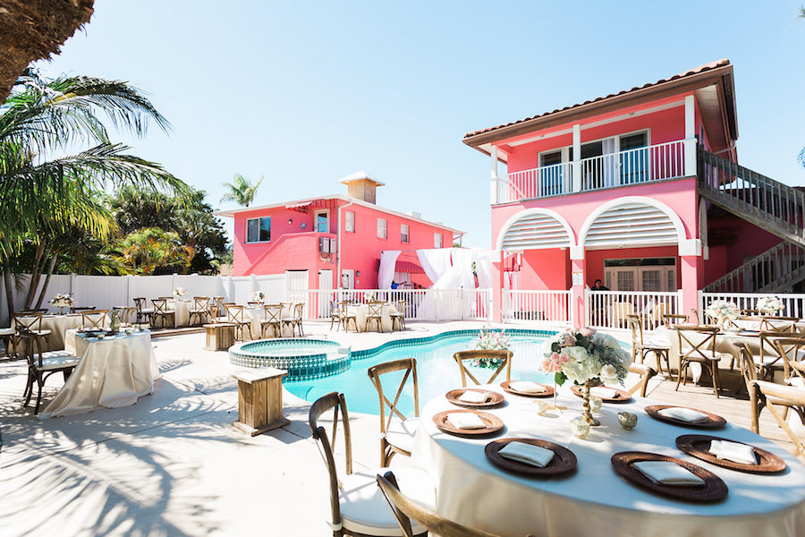 Reception Decor for Retro Inspired Beach Villa Poolside Wedding with Wooden Chairs and Floating White and Pink Tropical Bouquet with Wild Greenery | Siesta Key Wedding Venue Tropical Breeze Resort | Sarasota Wedding Planner Parties A La Carte