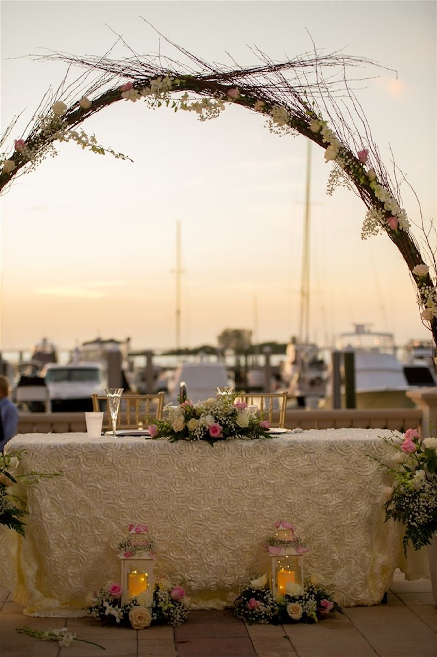 Waterfront Wedding Reception Decor with Sweetheart Table Natural Branch Arch with Baby's Breath and White and Pink Roses and Greenery with Lanterns   Tampa Bay Wedding Venue Westshore Yacht Club