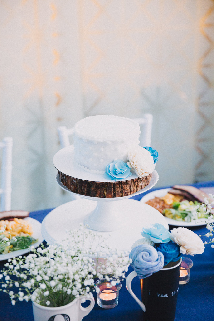 Bride and Groom Wedding Reception Blue and White Table Decor with Baby's Breath, Small Blue and White Flower Centerpiece, and Small Round White Wedding Cake on White Cake Stand