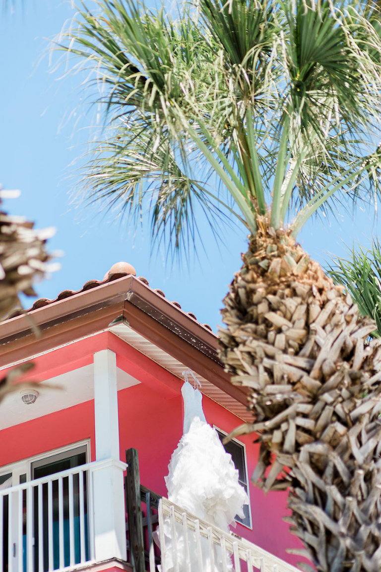 Siesta Key Wedding Venue Tropical Breeze Resort Wedding Dress Hanging on Open Porch of Pink Beach Villa