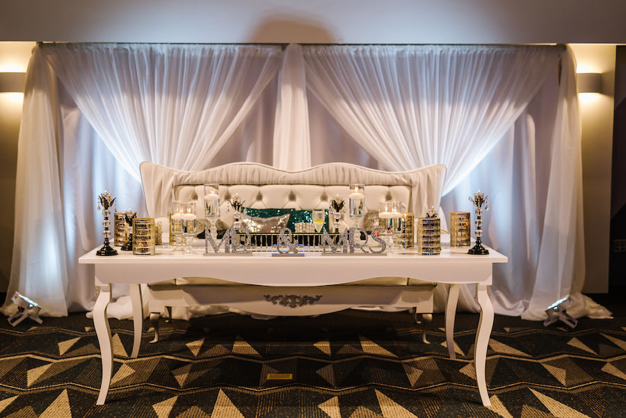 Bride and Groom Wedding Reception Table Vintage 1920s Inspired Wedding with Silver Glitter Mr and Mrs Sign and Stylish White Couch and Short Silver Vases