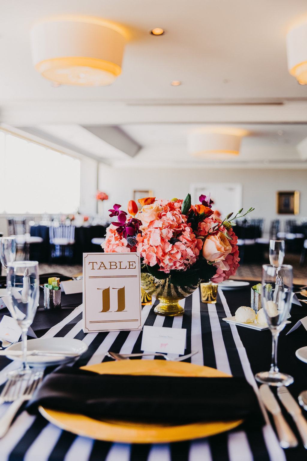 Black, White, and Gold Wedding Reception Table Decor with Elegant Printed Table Number Card, Low Tropical Floral Centerpiece in Round Gold Vase, and Striped Table Runner   Private Tampa Bay Wedding Venue The Centre Club