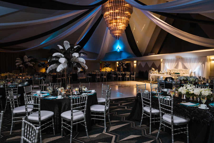 Roaring 20s Themed Black and Silver Wedding Reception with Tall Feather Centerpiece, Silver Chiavari Chairs, Black Linen, and White and Black Ceiling Drapery   Tampa Bay Wedding Venue Ruth Eckerd Hall