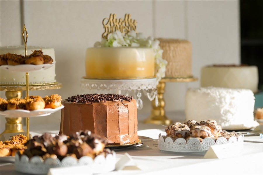 Desert Table with Multiple Cakes and Treats on Gold and White Platters and Gold Mr and Mrs Cake Topper