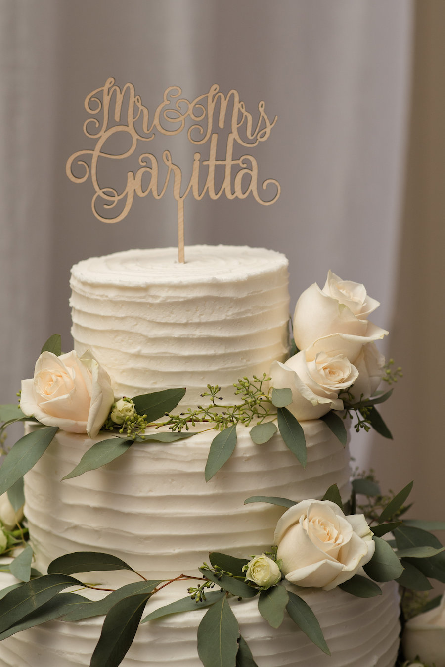 Round White Three Tier Wedding Cake with Cream Roses and Greenery and Stylish Mr and Mrs Gold Cake Topper