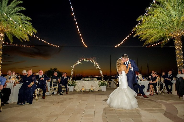 Outdoor Nighttime First Dance Portrait at Waterfront Wedding Reception with Edison Bulb String Lights and Floral Arch | Tampa Bay Wedding Venue Westshore Yacht Club | Photographer Andi Diamond Photography