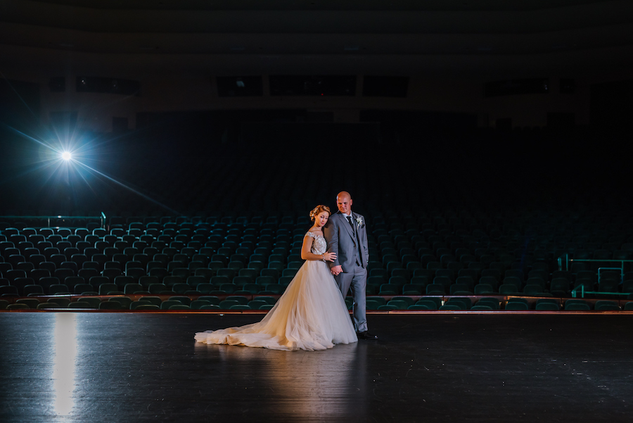 Bride and Groom Nighttime Wedding Portrait on Empty Stage at Tampa Bay Wedding Venue Ruth Eckerd Hall