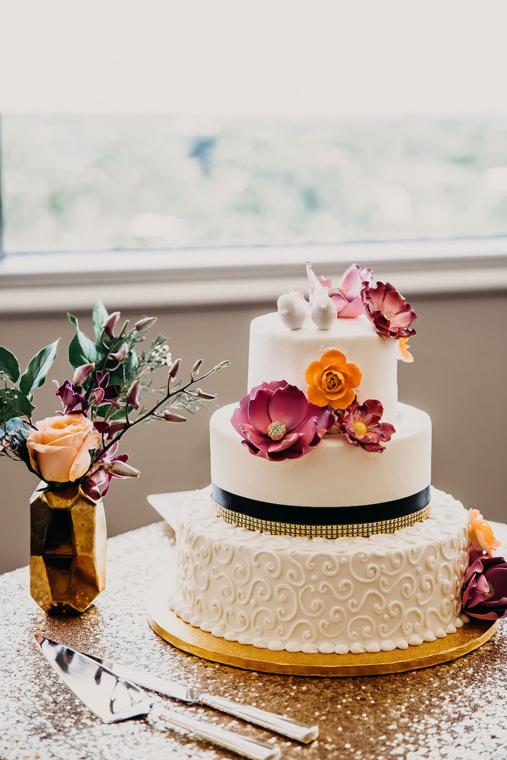 Three Tiered Round White Wedding Cake with Curly Cue Frosting and Black and Gold Stripe with Tropical Fuchsia and Orange Flowers on Gold Cake Stand   Tampa Bay Wedding