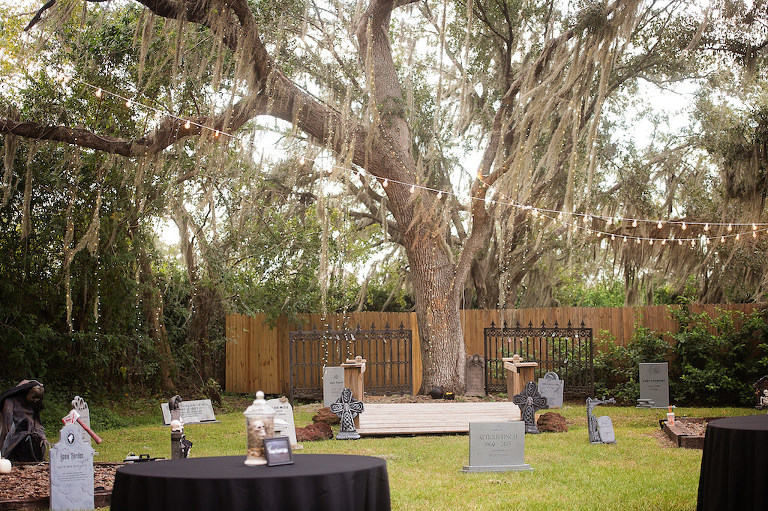 Halloween Themed Wedding Reception Decor with Tombstones and Black Linens and String Lights