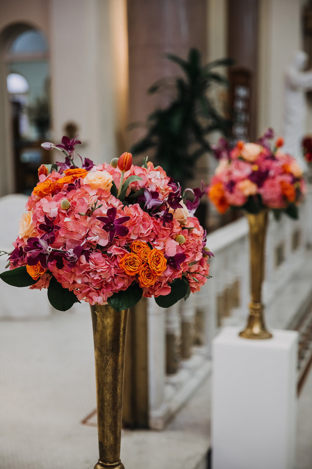 Tall Tropical Wedding Ceremony Flowers with Pink, Orange, and Purple Orchids in Gold Vases