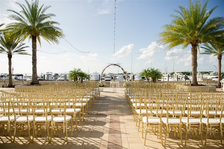 Waterfront Wedding Ceremony Decor at South Tampa Wedding Venue Westshore Yacht Club with Floral Arches and Gold Chiavari Chairs