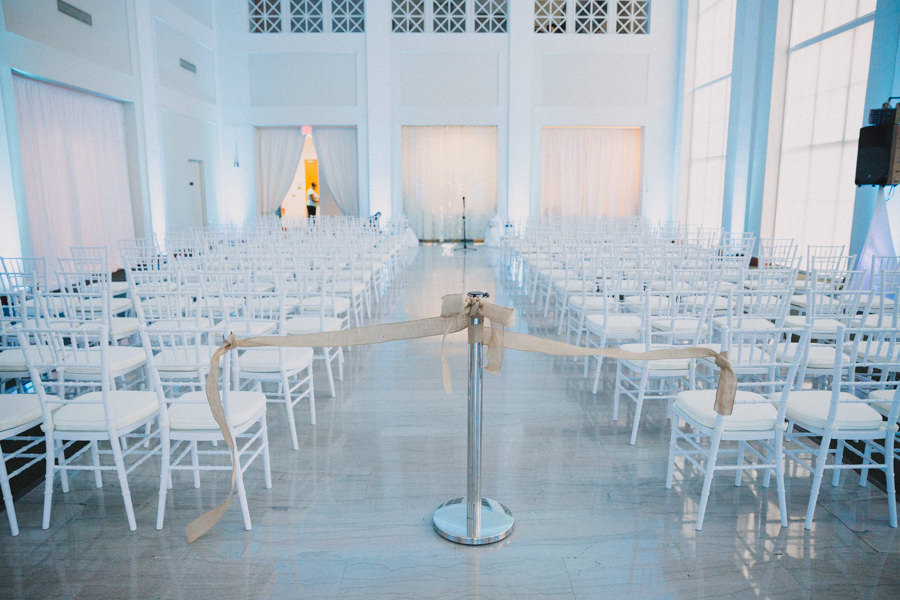 Wedding Ceremony Decor with White Chiavari Chairs and Gold Ribbon   Tampa Bay Wedding Venue The Vault