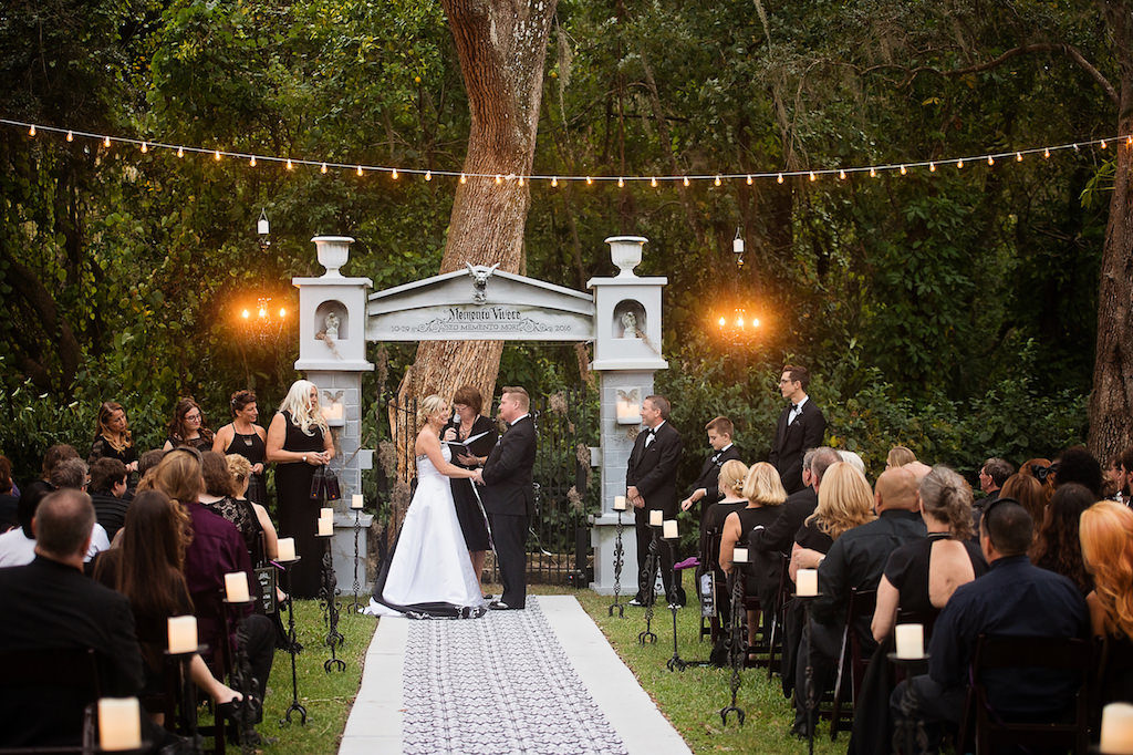 Outdoor Wedding Ceremony Portrait with Black and White Strapless Wedding Dress and Halloween Decor Tombstone Ceremony Arch and Black and White Fabric Aisle | Bradenton Wedding Planner Special Moments Event Planning