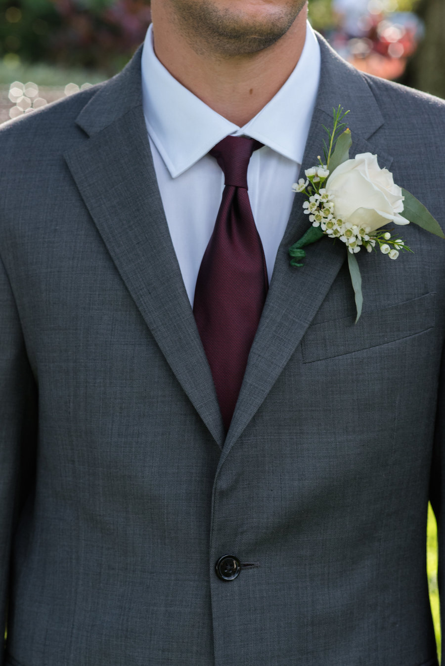 Groom Portrait with Grey Suit, Blue Shirt, Bordeaux Tie and White Rose with Babys Breath and Greenery Boutonniere