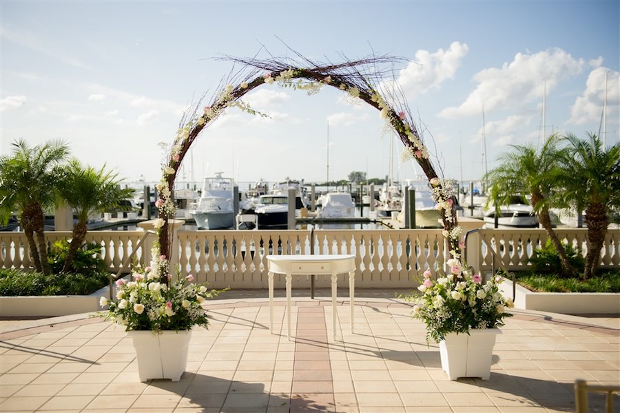 Waterfront Wedding Ceremony Decor with Natural Branch Arch and White and Pink Floral Decor   Historic Tampa Bay Wedding Venue Westshore Yacht Club