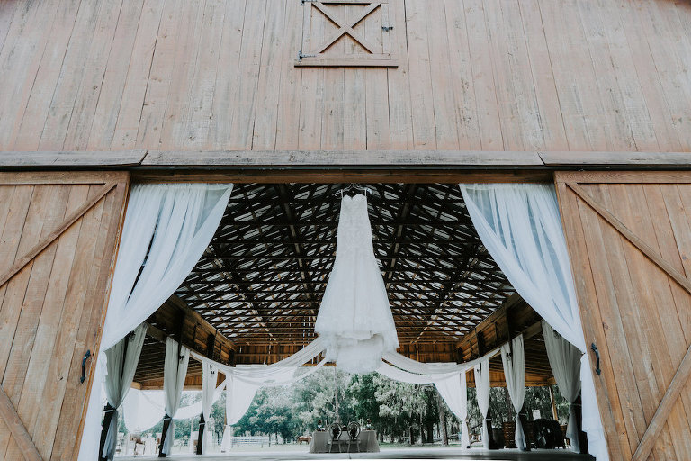 Rustic Barn Wedding Reception with White Draping and Wedding Dress on Hanger