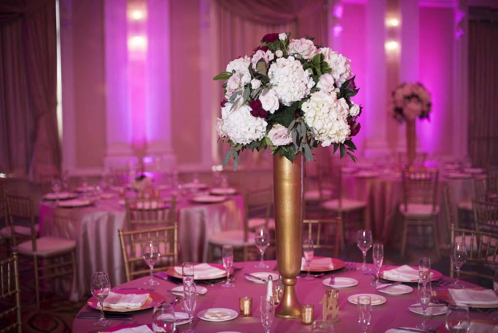 Ballroom wedding reception with tall gold centerpiece vase