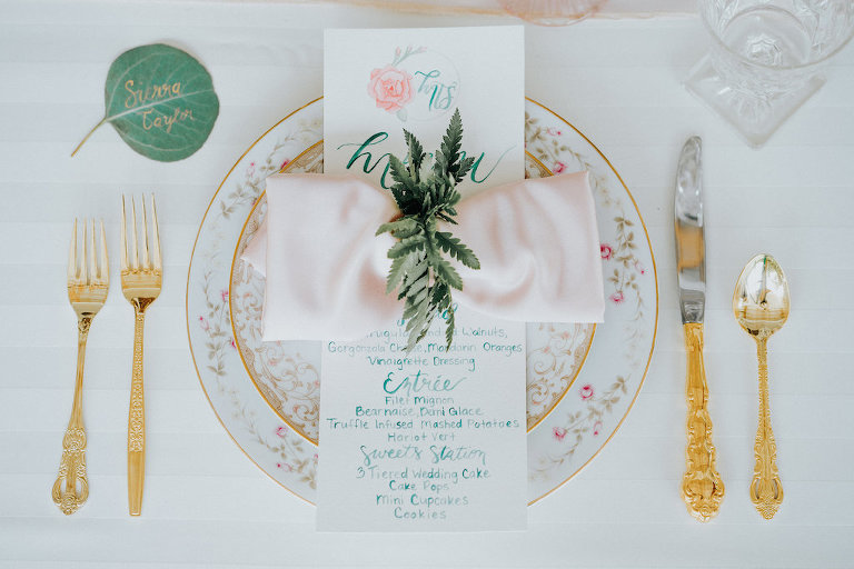 Elegant Rustic Wedding Reception Table Setting with Antique Gold Silverware and Painted Floral Plates, Hand-painted Leaf Place Card and Blue and Pink Menu, Blush Pink Napkin with Fern Napkin Ring | Sarasota Wedding Rentals Ever After Vintage Weddings