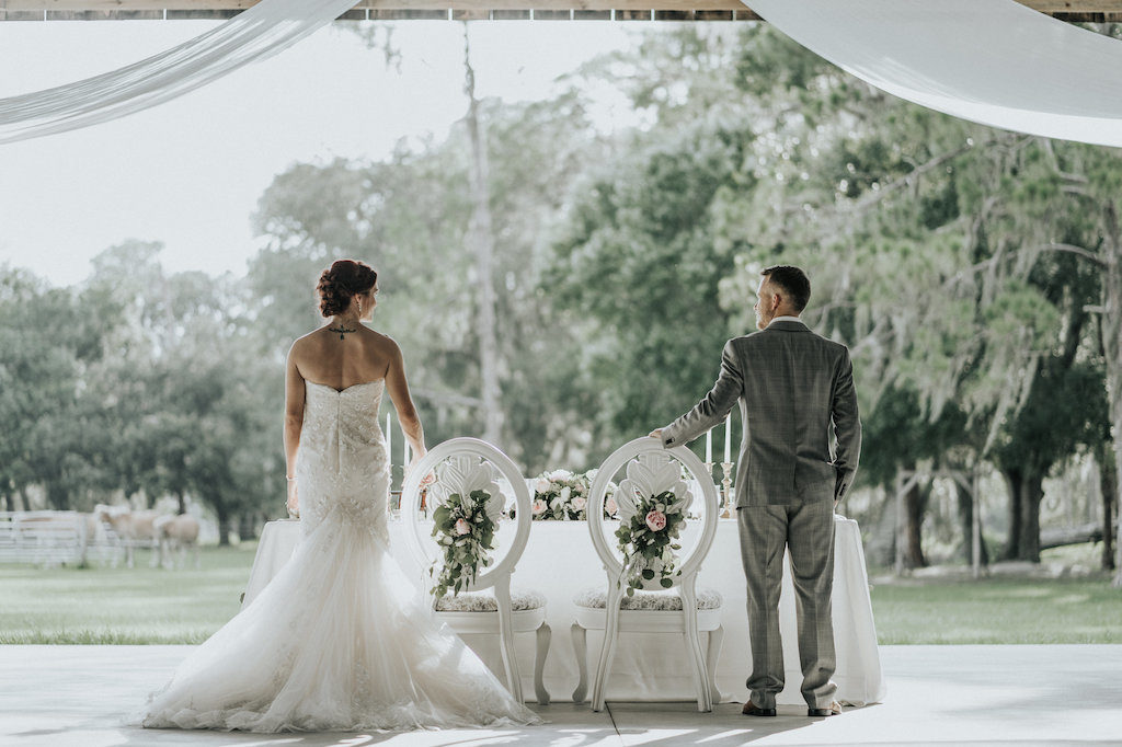 Rustic Barn Wedding Reception Bride and Groom Portrait with Antique White Chairs with Roses and Greenery and White Drapery | Sarasota Wedding Planner Kelly Kennedy Weddings and Events