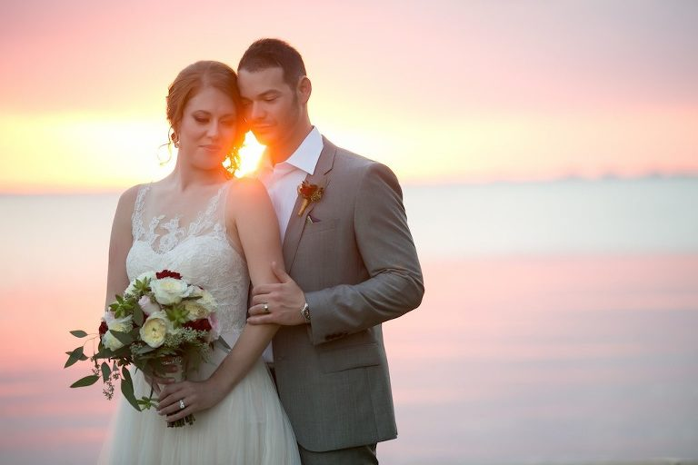 Waterfront Sunset Wedding Portrait with White, Pink, and Red Rose Bridal Bouquet with Greenery and Red Rose Boutonniere | Tampa Bay Florida Wedding Photographer Andi Diamond Photography | Hair and Makeup Michele Renee The Studio