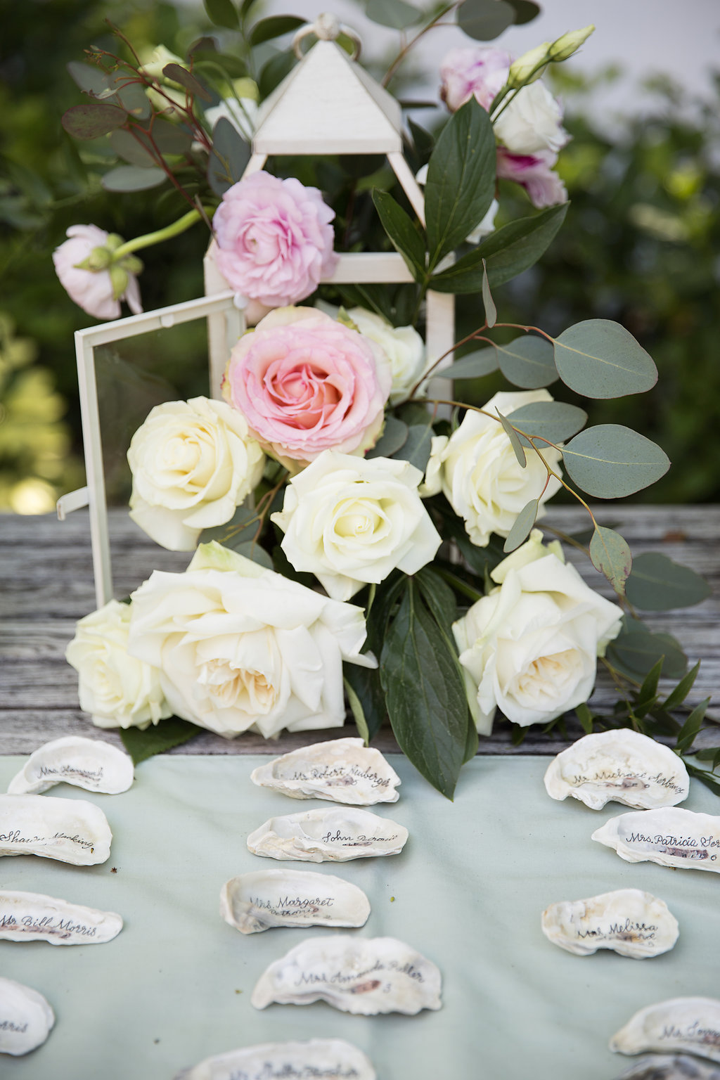 Wedding Reception Escort Card Table with Names Painted on Shells, with Ivory and Pink Rose Bouquet with Greenery in Lantern | Tampa Bay Florida Wedding Decor