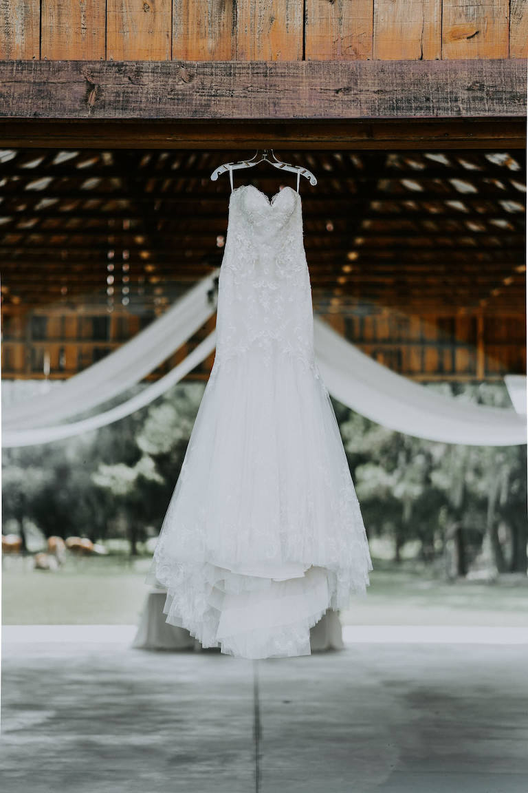 Rustic Barn Wedding Reception Venue with Sweetheart A Line Wedding Dress on Hanger
