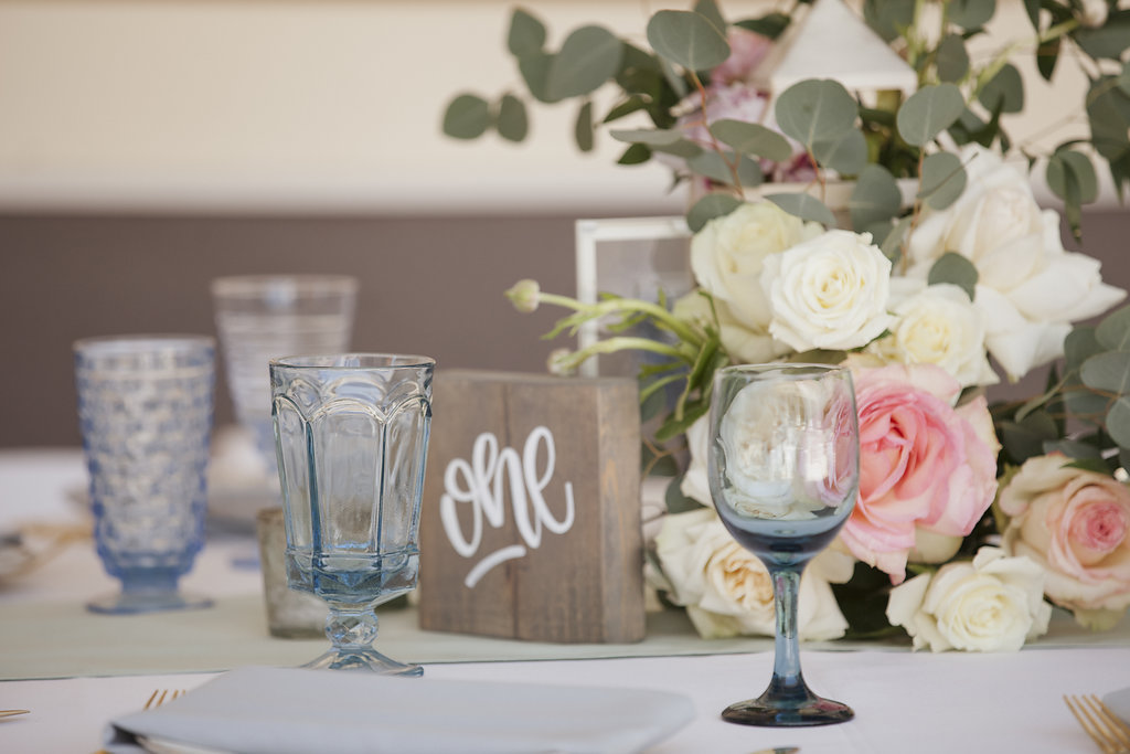 Romantic Vintage Outdoor Wedding Reception Decor | Mismatched Glassware and Wood Block Table Numbers and Greenery Centerpieces | Sarasota Reserve Vintage Rentals