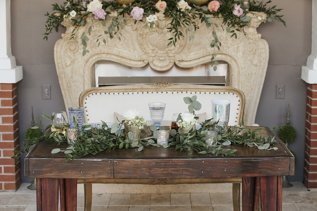 Romantic Vintage Outdoor Wedding Reception Decor | Wood Sweetheart Table with Tufted Upholstered Couch and Greenery Centerpieces | Sarasota Reserve Vintage Rentals