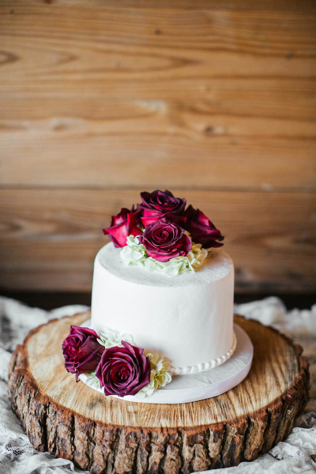 Round Single Tier Wedding Cake With Burgundy Roses On Natural Wood