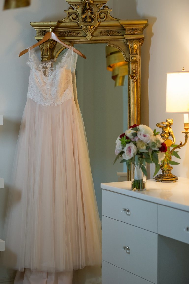 Blush Wedding Dress on Hanger with Pink White and Red Rose Bridal Bouquet