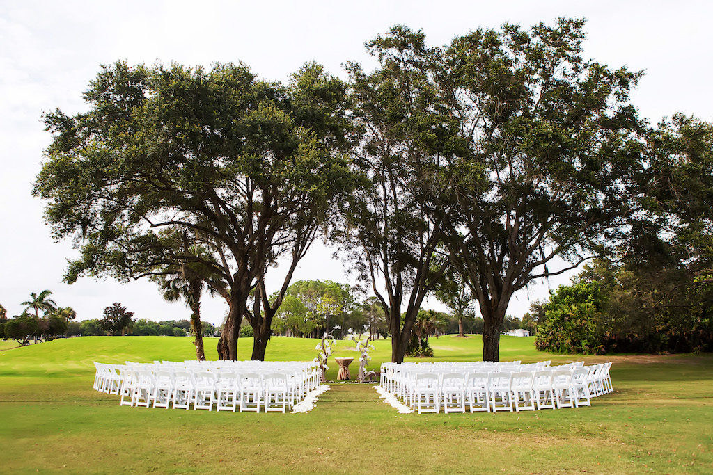 Outdoor Ceremony With Natural Driftwood and Floral Arch and White Folding Chairs | Tampa Bay Wedding Venue Countryside Country Club