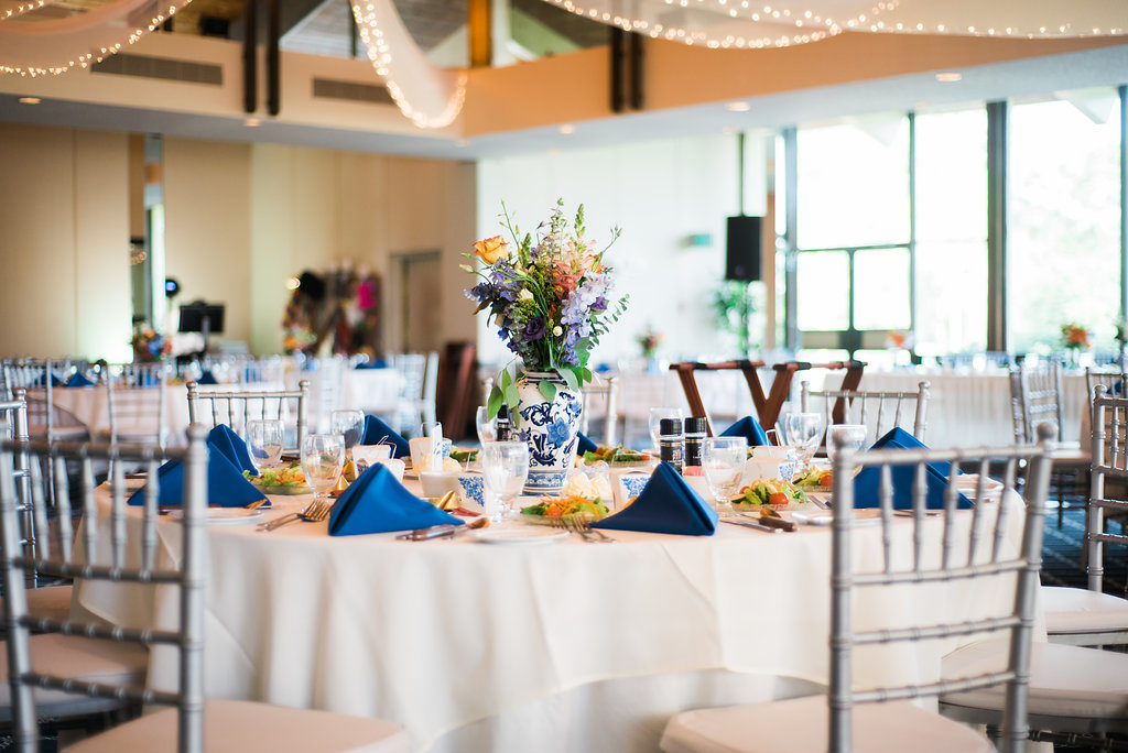 Blue Vintage Asian Inspired Wedding Decor with Colorful Orange and Purple Flower Centerpieces in Antique Vase | Venue St. Petersburg Country Club