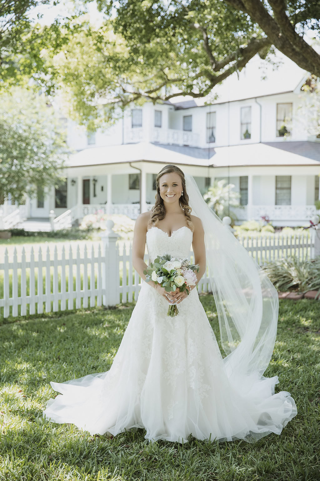Outdoor Garden Bridal Portrait with White and Greenery Bouquet, Sweetheart A-Line Dress with Cathedral Train and Long Veil | Florida Wedding Venue Palmetto Riverside Bed and Breakfast