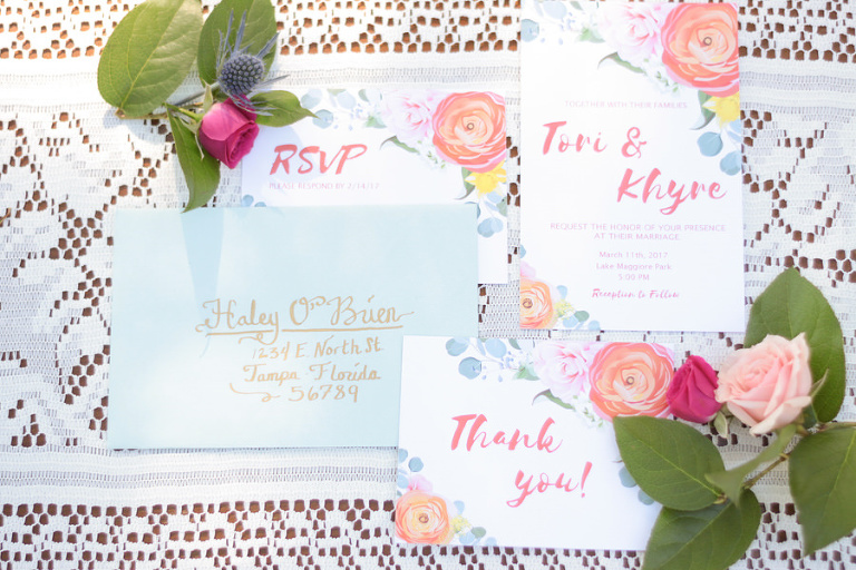Summer Floral Wedding Invitation Suite with Light Blue Envelope, Pink and Gold Hand Lettering, and Peach and Yellow Roses