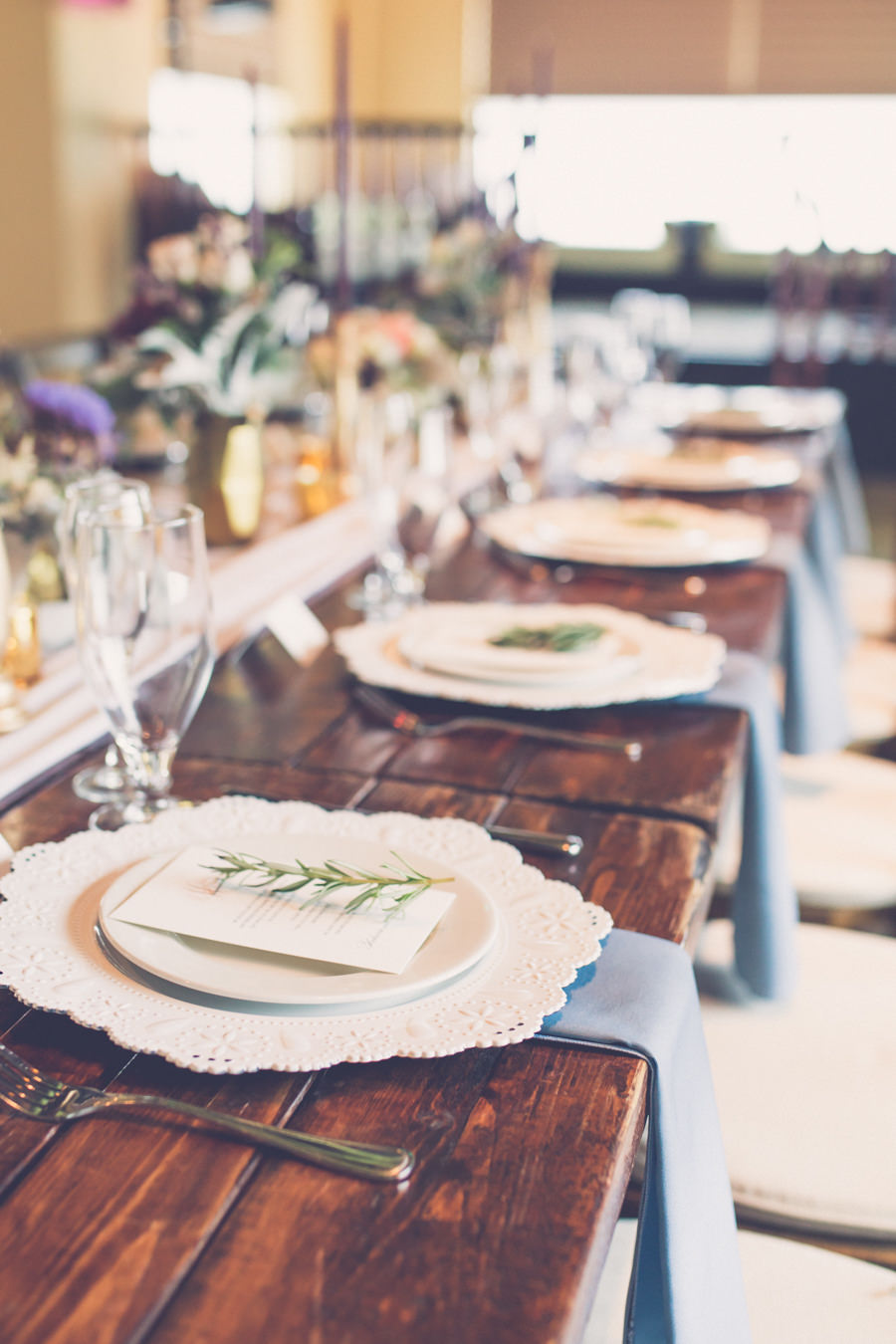 Boho Wedding Reception Table Decor with Long Wooden Table with Blush Runner, Gray Napkins, Gold Accents, and Lace Porcelain Chargers with Rosemary | Tampa Farm Table Rentals A Chair Affair